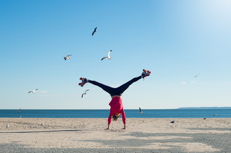 rollerskates: Happy young woman doing cartwheel on the beach wearing rollerskates. Young sportive woman wearing rollerskates and doing gymnastics on the beach in a bright sunny day. Portrait of woman on the beach doing a handstand with sea and seagulls in background. Stock Photo