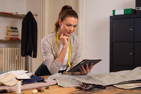 El diseñador de moda que usa el ordenador tableta digital en el estudio. costurera joven que trabaja en la tablilla digital para diseños de vestidos. Sastre pensar en un diseño con ayuda de ordenador tableta.