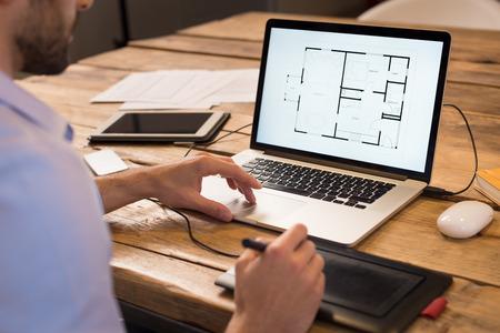 Close-up van een jonge interieurontwerper die in kantoor werkt. Architect werken op laptop bij nieuw huis project met grafische tablet. Binnenlandse ontwerper studie indeling van zijn huis project op computer. Stockfoto