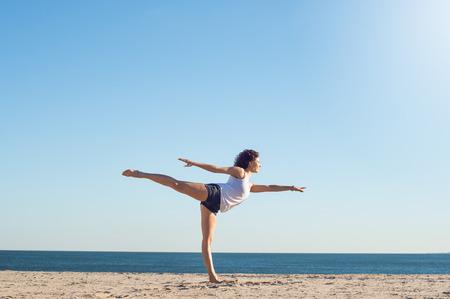 若い女性の美しい午前中にビーチでヨガを行います。美しい若い女性のビーチでヨガ中にストレッチします。若い女性がビーチでヨガのストレッチ