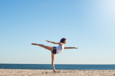 Young woman performing yoga on the beach during a beautiful morning. Beautiful young woman stretching during yoga on the beach. Young woman balancing on one leg in yoga stretch position at the beach. Stock Photo