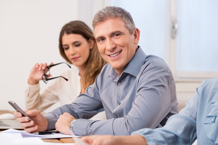 manager team: Portrait of mature business man looking at camera during a meeting. Senior man using mobile phone while looking at camera and smiling. Portrait of executive businessman with his colleaugues.