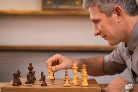 jugando ajedrez: gerente senior jugar al ajedrez en la oficina. hombre de negocios maduros pensando en su siguiente movimiento en el ajedrez. El liderazgo que goza de su siguiente movimiento en el ajedrez. Estrategia y concepto de gesti�n. Foto de archivo