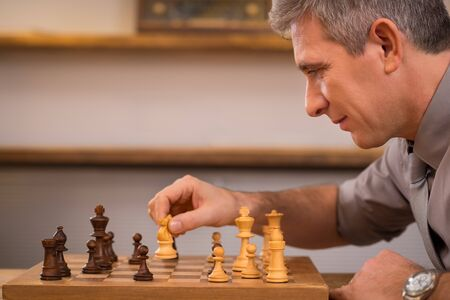 business game: Senior manager playing chess at office. Mature business man thinking over his next move in chess. Leadership enjoying his next move in chess. Strategy and management concept.