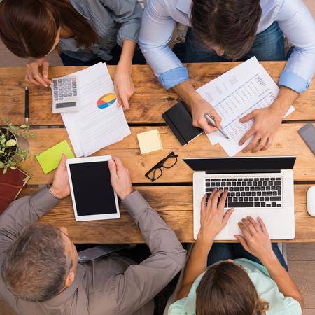 reunion de trabajo: Los empresarios analizar esquemas y diagramas. hombres de negocios exitosos que trabajan con documentos en la oficina. Grupo de empresarios que trabajan juntos en la oficina.