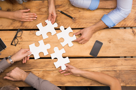 business puzzle: Close-up of businesspeople solving jigsaw puzzle. Closeup of business people wanting to put four pieces of puzzle together. Businesspeople trying to solve problem with the help of jigsaw puzzle. Stock Photo