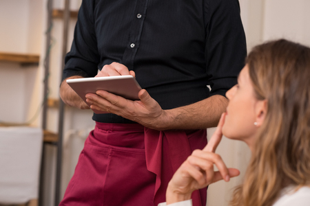 servings: Close up of waiter's hand noting down menu on tablet. Young woman ordering for food to a waiter at restaurant. Young beautiful woman thinking of food to order in front of a waiter holding tablet. Stock Photo