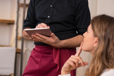 Zblízka číšníka ruky zmínku down menu na tabletu. Mladá žena objednání na jídlo, aby číšník v restauraci. Mladá krásná žena myšlení jídla na objednávku v přední části číšník držení tabletu.