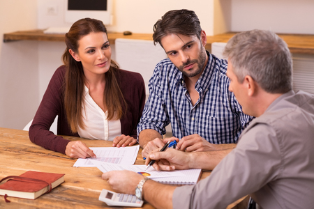 Businessman explaining loan policy to young couple. Happy young couple discussing with a financial agent their new investment. Financial consultant presents bank investments to a young couple. Archivio Fotografico