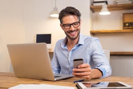 젊은 행복 사업가 그의 스마트 폰을 읽는 동안 웃 고. 사무실에서 smartphone으로 메시지를 읽고 웃는 비즈니스 사람의 초상화. 사무실에서 그의 책상에서