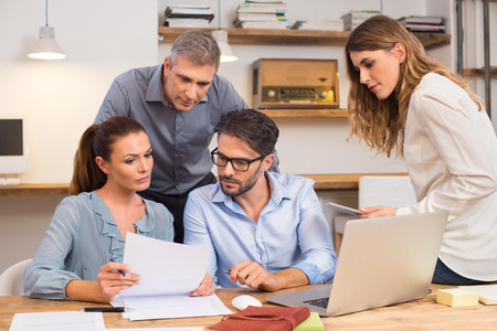 merger: Business team discussing on document and idea at meeting. Businesspeople looking at past history of a company for merger. Meeting in office between creative people, casual business.
