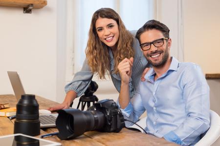 Los fotógrafos profesionales con la cámara y el ordenador portátil de trabajo en el estudio. Fotógrafo con asistente sentado en la oficina y mirando a la cámara. Equipo de fotógrafos que trabajan juntos.