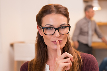 Portret van een aantrekkelijke vrouw met de vinger op de lippen. Jonge zakenvrouw met bril in het kantoor vraagt om stilte tijdens het team dat werkt in de achtergrond. Vrouw met vinger op lippen gebaren voor vrij.