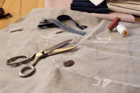 tailor suit: Composition of needle and thread with other sewing tailoring tools. Spool of thread, scissors, buttons,sewing supplies. Close up of scissor, buttons, thread and thimble on fabrics.