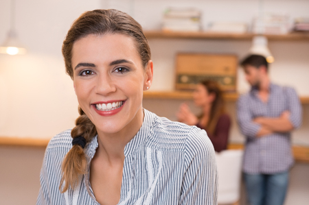 Confident young businesswoman with colleagues standing on background. Confident and smiling business woman with group of business people meeting in office. Portrait of a smiling woman posing and looking camera.