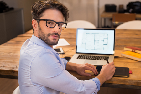 designer working: Portrait of a young interior designer working at office. Man working on laptop turning around towards camera. Happy architect studying layout on laptop at desk and looking at camera with satisfaction Stock Photo