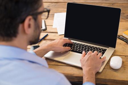 노트북 화면 앞에 앉아 사업가의 다시보기. 사무실에서 현대 노트북에 입력하는 사람. 나무 테이블에 앉아 컴퓨터에 젊은 학생 입력합니다.