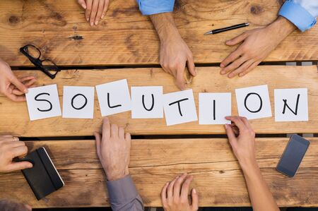 Businesspeople arranging placards on wooden table forming the word solution. White cards strategy used by businesspeople. Businesspeople find the right solution for their problem. Stock Photo
