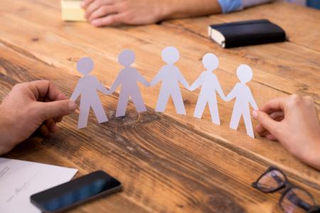 Nahaufnahme der Hände von Mann und Frau hält Papier Menschen Kette. Zwei Geschäftsleute mit Papier Mann Kette darstellt, Solidarität und Freundschaft. Nahaufnahme von Symbol der Einheit und Stärke und Zusammengehörigkeit.