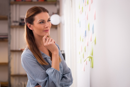 Gelukkige vrouw die een plak notities op de muur. Geconcentreerde vrouw kunstenaar kijken naar kleurrijke sticky notes op kantoor. Jonge ontwerper kijken op kleverige nota's over wallin creatieve kantoor.