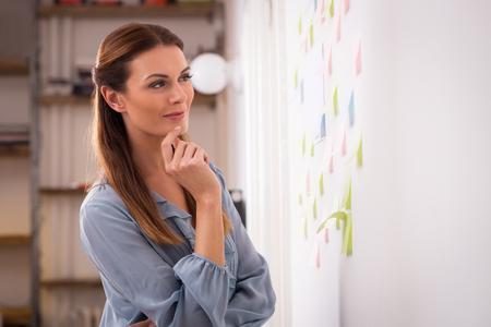 Mujer feliz mirando a las notas adhesivas en la pared. Concentrado mujer del artista mirando notas adhesivas de colores en la oficina. El diseñador joven mirando hacia arriba en notas adhesivas en la oficina creativa Wallin.