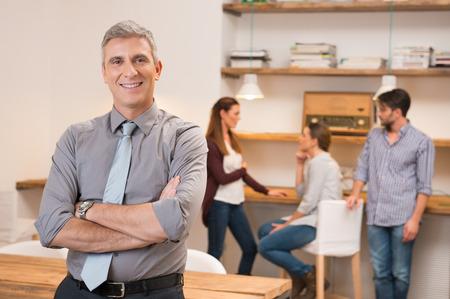 Confidentes de alto nivel de negocios de mantenimiento y de pie con los brazos cruzados. hombre de negocios seguros y sonriente con un grupo de hombres de negocios reunidos en la oficina en el fondo. Retrato de un líder sonriente mirando a la cámara.
