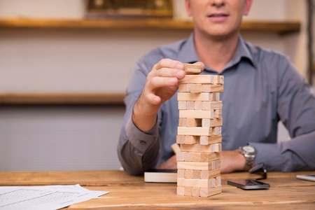 building bricks: Businessman thinking of expansion with the help of building wooden bricks. Leader gambling placing wooden block on a tower. Business man trying to find a solution to problem by building with wooden bricks.