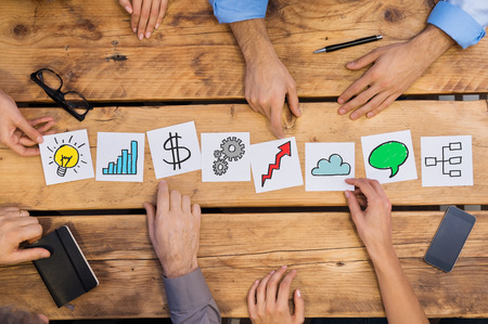 Imprenditori che organizzano diversi concetti di business sul tavolo di legno. strategia bianco carte usato da uomini d'affari. Uomini d'affari brainstoring di nuove soluzioni pur ponendo diverse carte in ufficio.