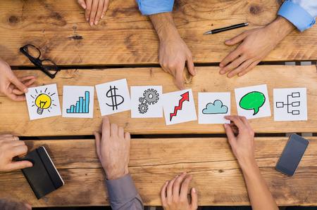 Ondernemers regelen van verschillende business concepten op houten tafel. Witte kaarten strategie gebruikt door ondernemers. Mensen uit het bedrijfsleven brainstoring naar nieuwe oplossingen terwijl het plaatsen van verschillende kaarten in het kantoor.