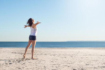 stretched out: Happy young woman with arms outstretched at beach on a bright morning. Beautiful young woman with arms stretched out standing on a beach. Happy young woman feelling good and relaxing at the beach.