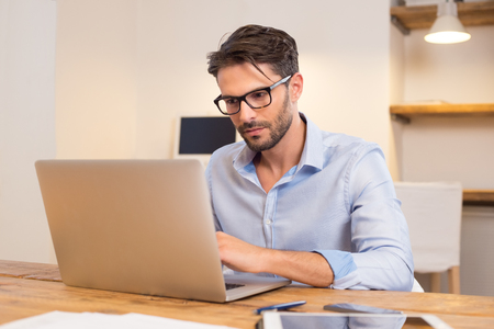 Young casual office worker working on laptop. Young businessman typing on laptop computer at office. Young man working absorbed on laptop at work place. Stock Photo