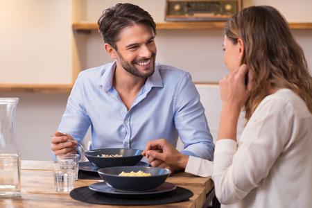 eten: Loving paar op zoek naar elkaar tijdens het lunchen. Close-up shot van de jonge man en vrouw met een diner thuis. Gelukkig jong koppel eten.