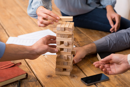 challenges: Close up of hands helping build a building of wooden pieces. Businesspeople planning a new business strategy. Business team trying to generate new ideas with the help of playing with wooden bricks. Business risk concept.