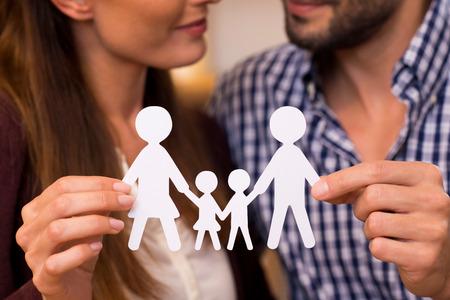 Primer plano de un hombre de papel cadena de explotación de pareja de una familia. joven pareja de decidir sobre la planificación familiar. Primer plano de la cadena hombre de papel de una familia. Padres manos que sostienen un documento de la familia.