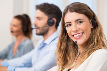 Sorridente femminile operatore di call center facendo il suo lavoro con un auricolare, mentre guardando la telecamera. Ritratto di donna felice in un call center sorridente e di lavoro. Ritratto di felice operatore di supporto clienti telefonico femminile sorridente sul posto di lavoro.