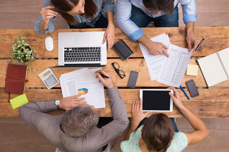 Vysoký úhel pohledu podnikatelů analyzujících schémat a diagramů. Obchodní tým analyzovat růst a minulé historii firmy. Podnikatelé v setkání diskutovat o vyhlídky do budoucna a strategií růstu v kanceláři. Reklamní fotografie