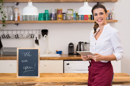 waitress: Portrait of young happy waitress looking at camera at bar with digital tablet. Portrait of a young female chef holding digital tablet with blackboard in kitchen corner. Young smiling woman in her small business shop.