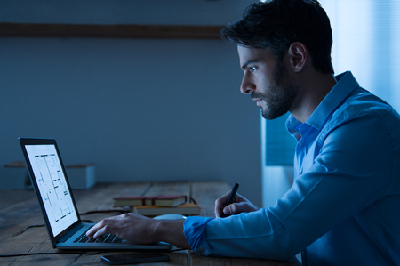 man at work: Architect sitting at night working on architectural plan on laptop. Young handsome interior designer in casual checking blueprint of a house on laptop. Architect studying the map and layout of a new project. Stock Photo