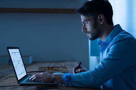 El arquitecto sentado en la noche trabajando en plan arquitectónico en la computadora portátil. Joven y guapo diseñador de interiores en el plan de comprobación informal de una casa en la computadora portátil. Arquitecto que estudia el mapa y el diseño de un nuevo proyecto. Foto de archivo - 51077849