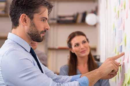 Young creative business team in office taking sticky notes from the wall. Businessman and businesswoman looking at post it on wall in office. Young business man looking sticking notes on wall in creative office.