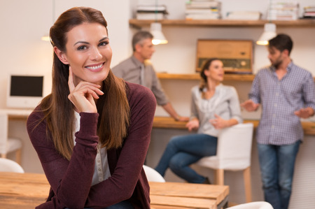 Happy and cheerful young woman looking at camera. Portrait of a beautiful smiling woman in office. Young casual woman sitting with hand near ear with colleagues in background. photo