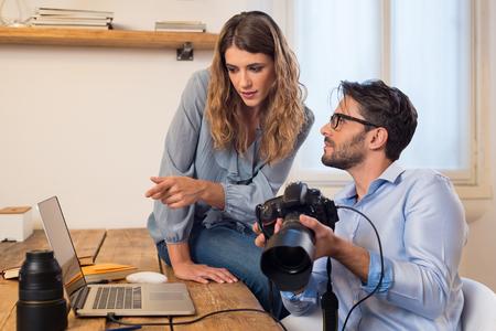 Fotógrafos jóvenes que buscan en las fotografías en la computadora portátil. Fotógrafo Asistente ayudar fotógrafo en la selección de fotos. Equipo joven de fotógrafo que trabaja en un estudio profesional. Foto de archivo