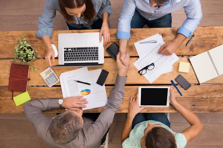 Wysoki kąt widzenia przedsiębiorców drżenie rąk i zamknięcia transakcji. Sukces pracy zespołowej pracy w biurze. Partnerów biznesowych siedzi w pracy tabeli i planowania.