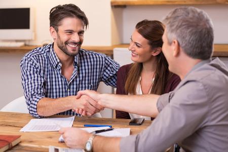 사무실에서 행복 한 젊은 부부와 함께 성숙한 관리자의 악수입니다. 기업인 서명 계약을 충족하는 동안 핸드 셰이크. 행복한 사람이 손을 흔들면서 그