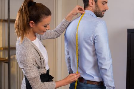 Tailor standing near male client measuring back. Tailor woman taking measures for new business shirt using tape meter. Young fashion designer taking measurement of man wearing shirt in store.