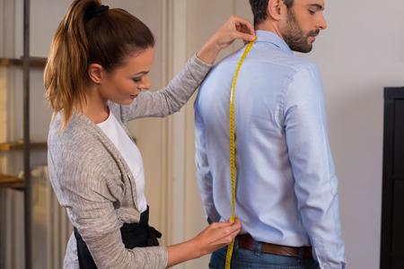Tailor stojącego obok męskiej klienta pomiaru powrotem. Tailor kobiety podjęły środki z nowej koszuli biznesu za pomocą licznika taśmy. Młody projektant mody pomiarem człowiek noszenie koszuli w sklepie. Zdjęcie Seryjne