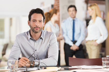 Portret van een jonge knappe zakenman bedrijf bril kijken camera in werkomgeving.