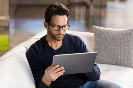 latin man: Portrait of a serious man wearing eyeglasses working on digital tablet at home.