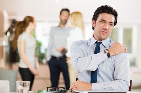 neck pain: Portrait of a businessman at work suffering from shoulder pain. Stock Photo
