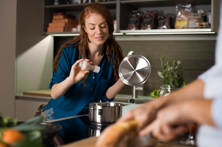 Bonne jeune couple cuisson et cuire repas à la cuisine.